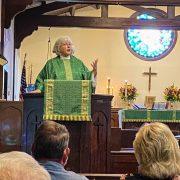 Rev. Cori preaching pulpit green